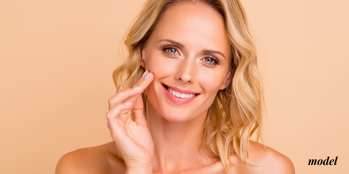 NaturalImage_DermalFillers_blonde_touching her face and smiling