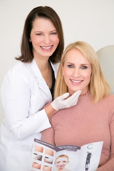 Dr. Sikorski Smiling At Camera While Touching Chin of Blond Female Patient In Pink Blouse