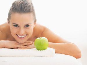 Female Laying on White Massage Table With Green Apple on Towel In Front of Folded Arms 1